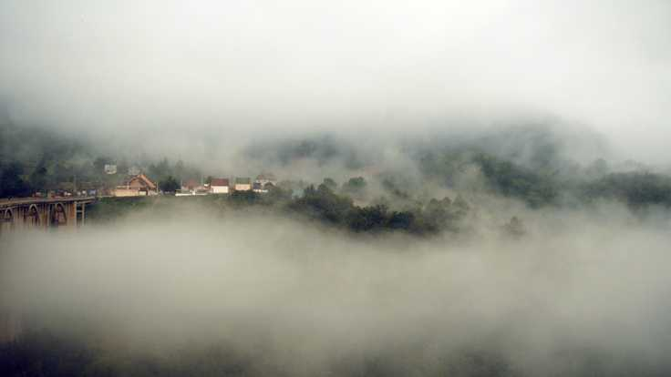 foggy cloudy high mountain view on small town