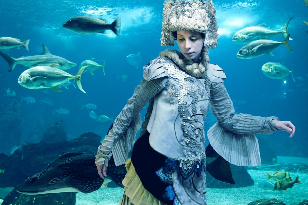 Girl in fairytale costume in fish tank
