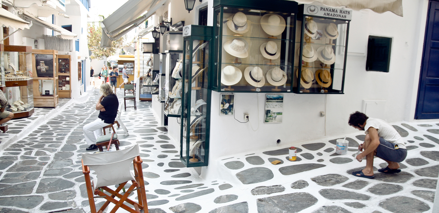Mykonos street with white painted tiles borders