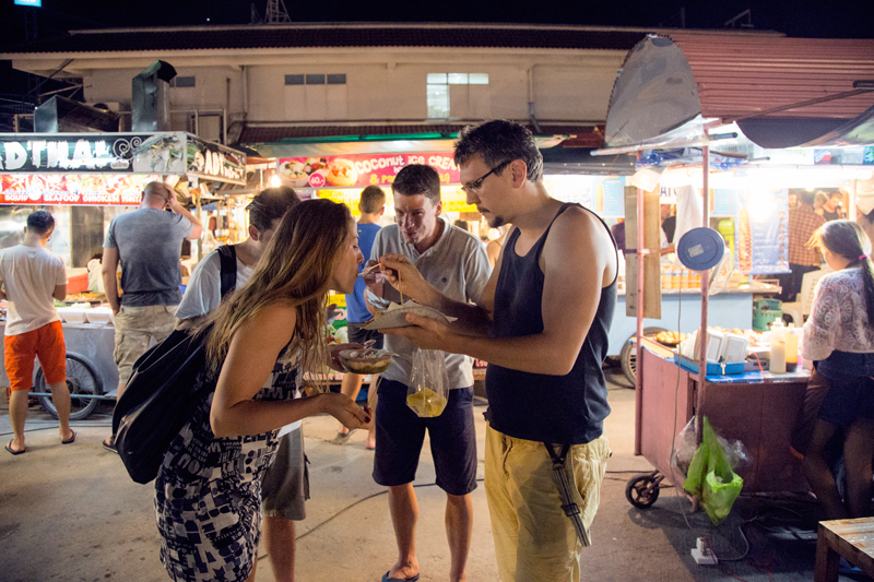 Guy feeding girl on food market