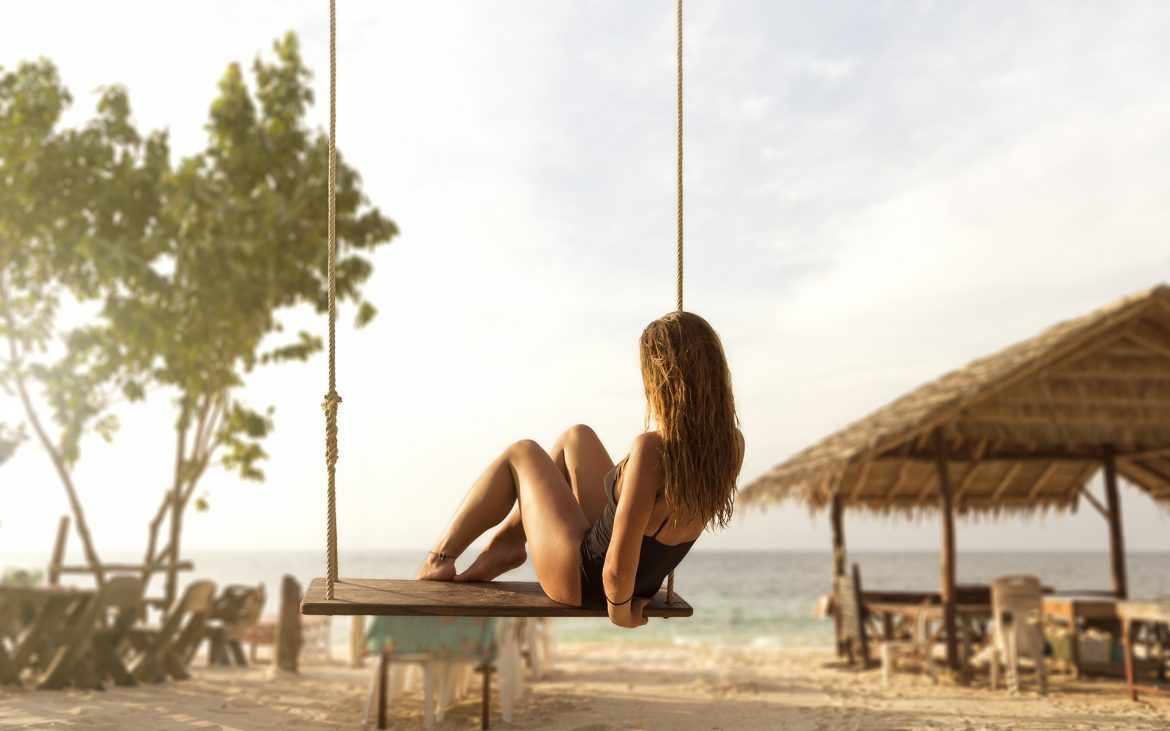 Girl_on_swing_in_beach_bar_from-back