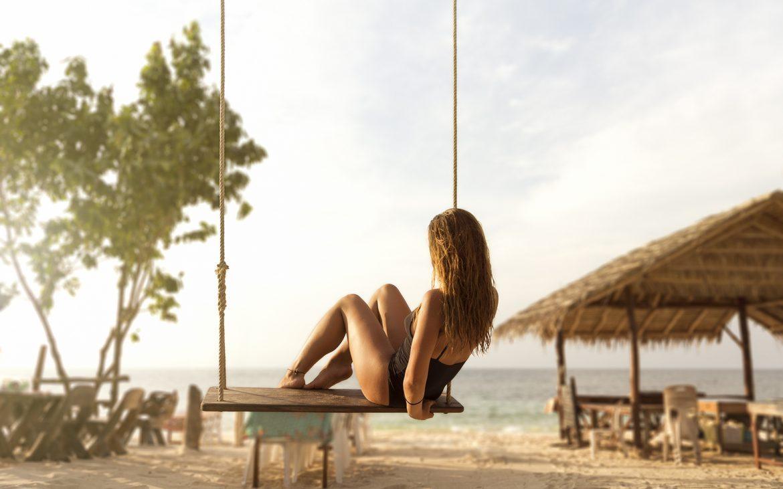 Girl_on_swing_in_beach_bar_from-back