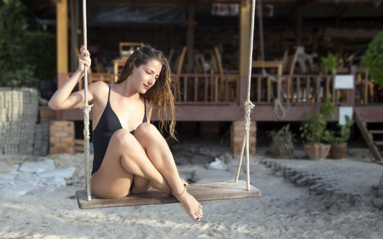 Girl_on_swing_in_beach_bar_looking_down