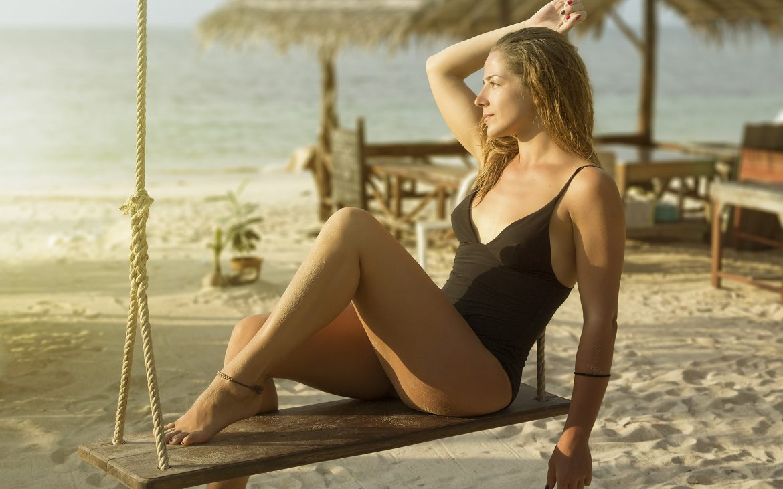 Girl swinging on the beach