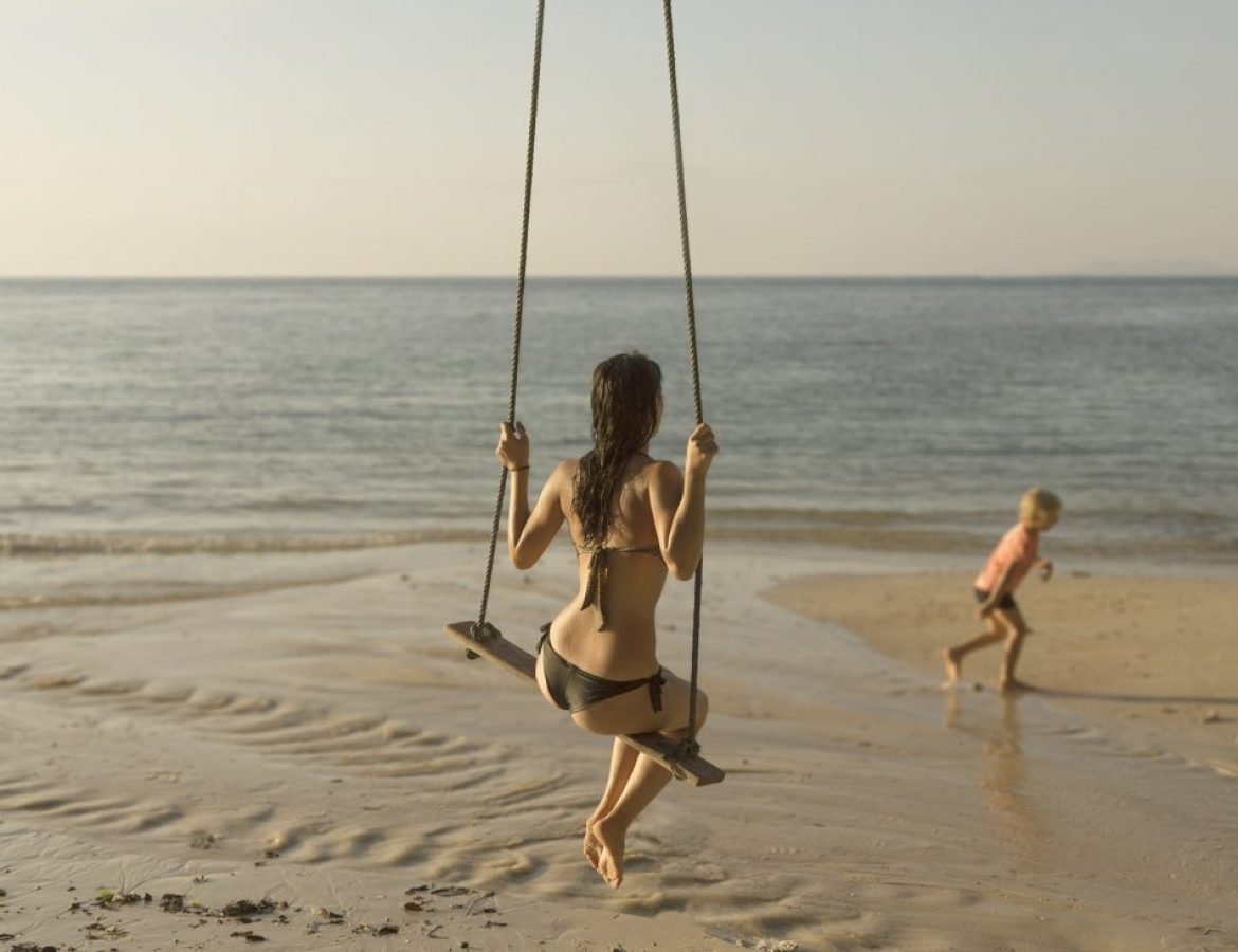 Girl_on_swing_on_beach_with_child_running