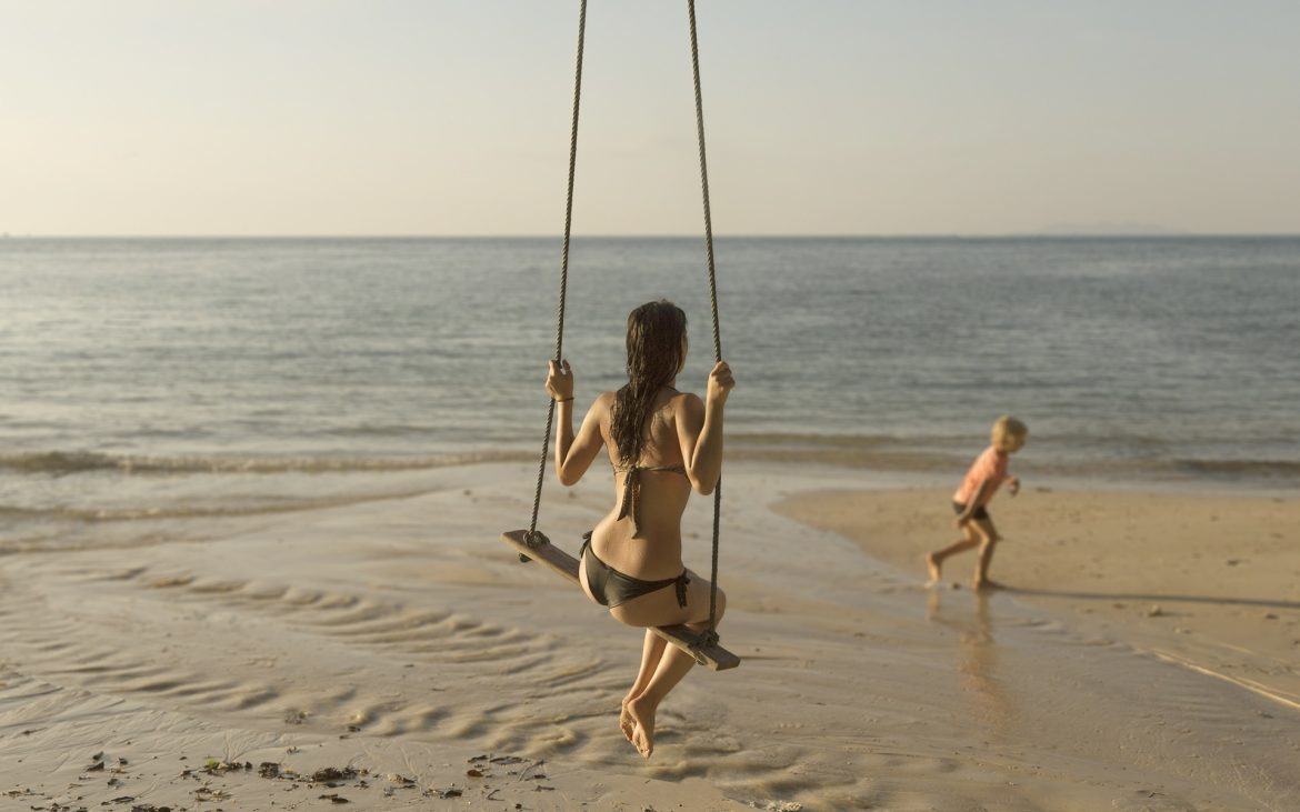 Girl swinging on the beach