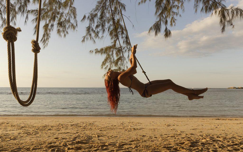 Redhead Girl swinging on the beach