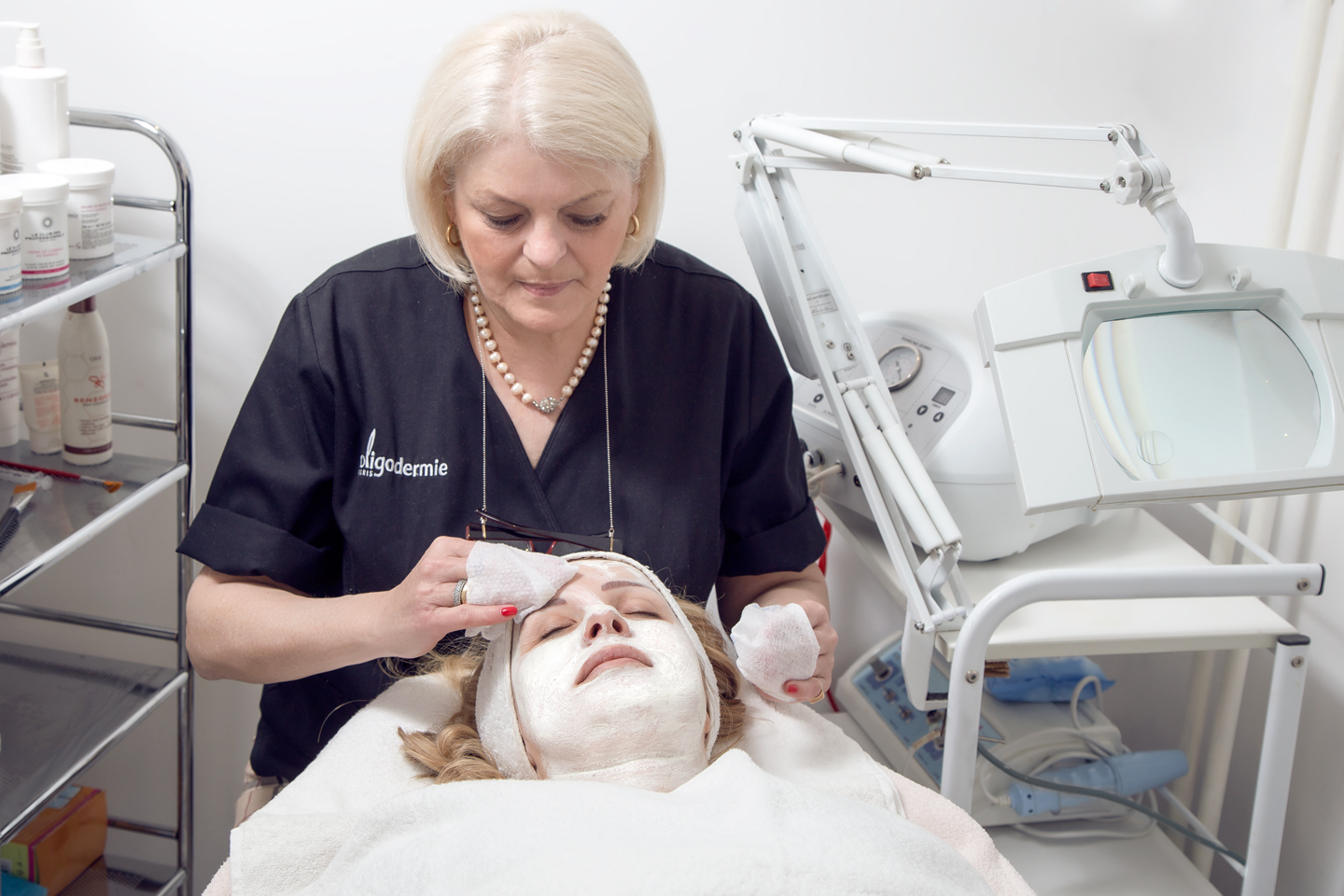 Cosmetologist placing face mask