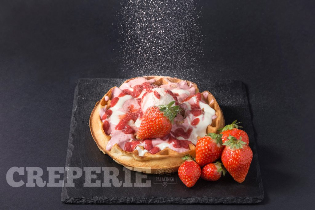 Waffle with strawberries and sugar powder falling