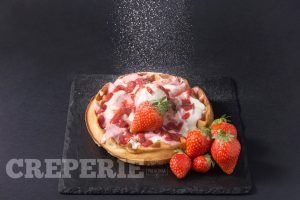 Waffle with strawberries and sugar powder falling