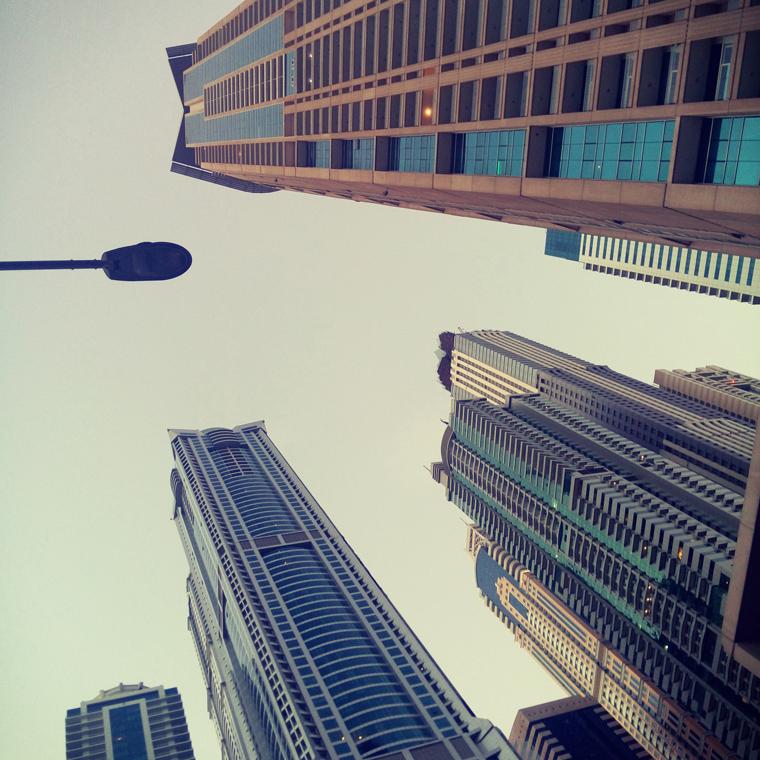 Pogled odozdo ka neboderima i nebu u Dubaiju