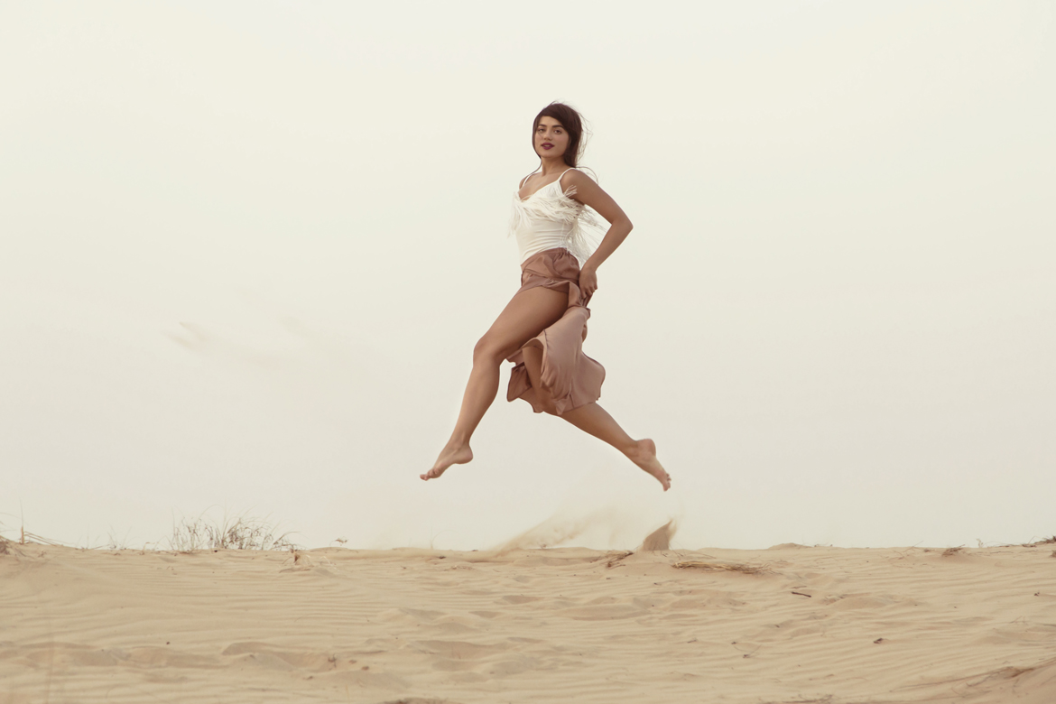 Beautiful girl model jumping above horison in desert