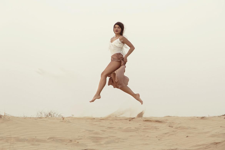 Beautiful girl model jumping above horison in desert