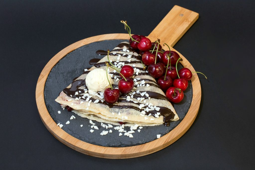 Plate with Sour Cherry cream and chocolate on crepe