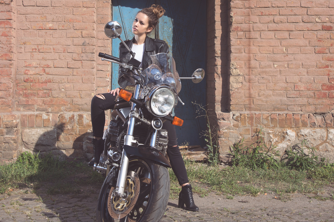 Girl on a motorbike with blue doors behind